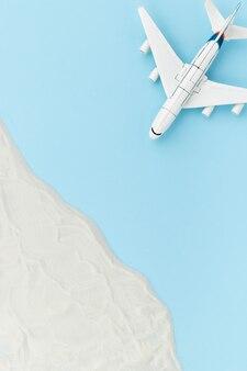 おもちゃの飛行機と砂を使ったクリエイティブな構成。旅行休暇のコンセプト