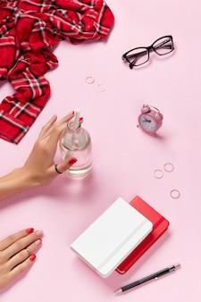 Креативная композиция с женскими руками и аксессуарами для планировщика над розовым столом