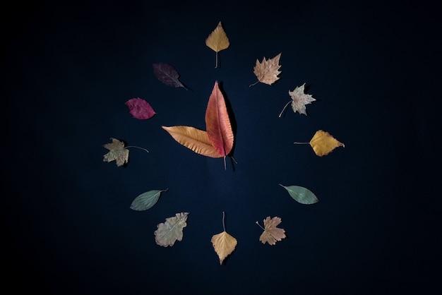 Креативная концепция часов из осенних листьев на черном фоне