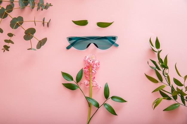 컬러 여름 배경에 선글라스 봄 여름 꽃으로 만든 창의적인 개념 여성 얼굴. 컬러 녹색 선글라스에 여성 만화 얼굴입니다. 평면도 평면도.