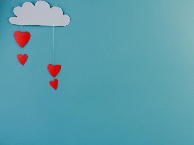 창의적인 컨셉의 휴일 발렌타인 데이는 파란색 배경에 마음으로 비가 내리는 수제 종이 구름의 사진을 사랑합니다.