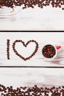 Creative concept of i love coffee sentence made of beans. roasted coffee grains in a heart shape. white wooden planks.