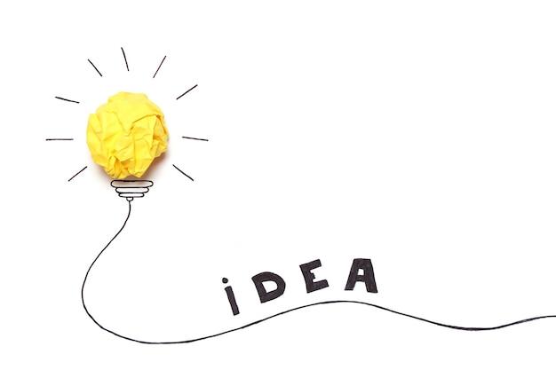 구겨진 종이 노란색 공으로 전구를 그린 창의적인 개념 아이디어 새로운 아이디어