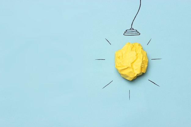創造的なコンセプトのアイデアは、しわくちゃの紙の黄色いボールで電球を描いた