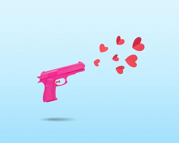ピンクの拳銃と赤い紙のハートで作られた創造的なコンセプト