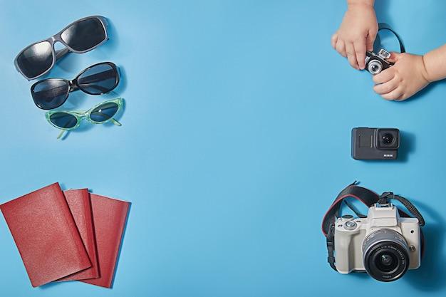 Креативная концепция плоского путешествия с фотоаппаратами, солнцезащитными очками и паспортами для семьи из трех человек концепция планирования семейного отдыха или поездки. скопируйте пространство.