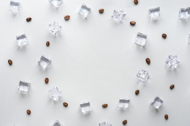 회색 배경에 아이스 커피의 창의적인 개념. 얼음 조각과 복사 공간이 있는 커피 콩.