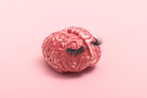 メンタルヘルスの創造的な概念。ピンクの背景に悲しい人間の脳。