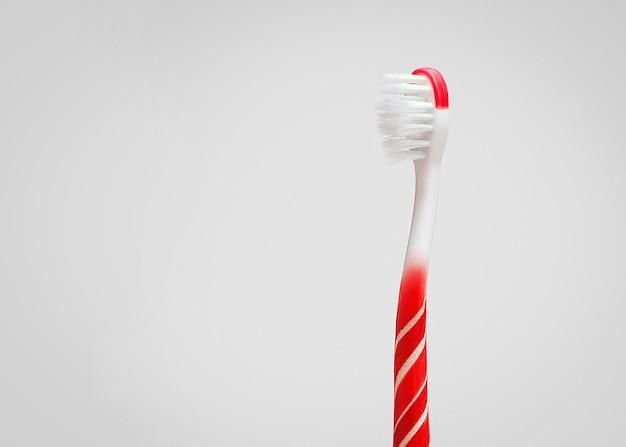 Креативная концепция гигиены полости рта. зубная щетка в форме леденца на палочке на сером фоне с копией пространства.