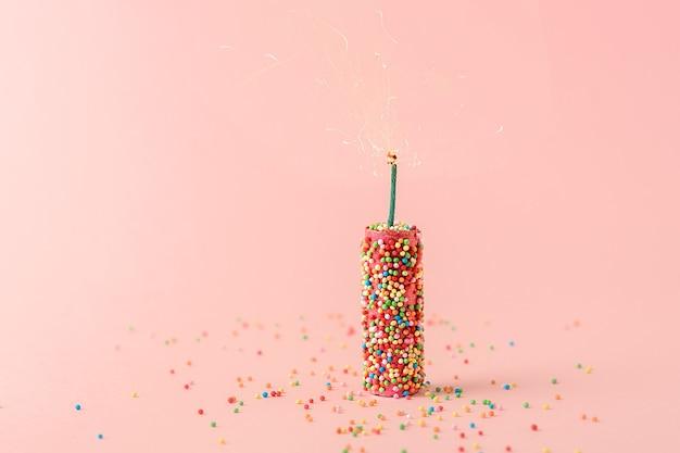 休日の創造的な概念。ピンクの背景に甘い風船とピンクの爆竹。