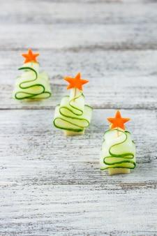 Креативная концепция устанавливает рождественские елки из огурца, сыра и звезды моркови. смешная детская еда для новогодней вечеринки на сером фоне с копией пространства