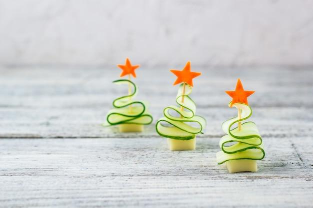 창조적 인 개념은 오이 치즈의 크리스마스 트리와 당근의 별을 설정