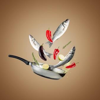 Креативная концепция со сковородой для гриля, свежей морской окунь и овощами