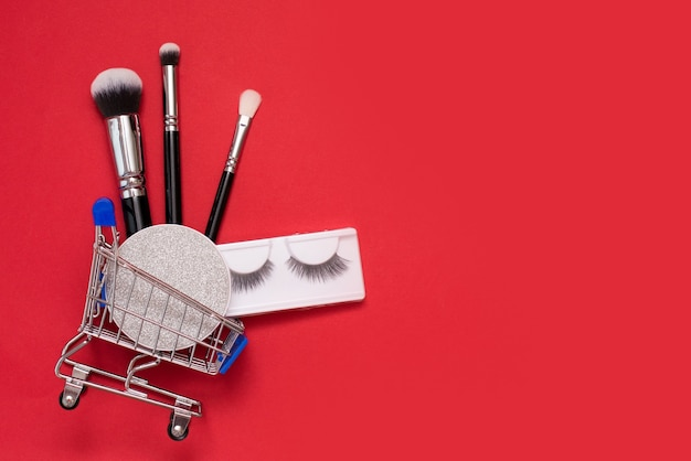 빨간색 배경에 화장과 쇼핑 트롤리와 창조적 인 개념. 브러쉬, 마스카라, 인조 속눈썹