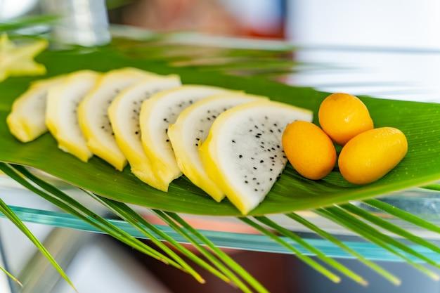 スライスしたエキゾチックなフルーツと緑の葉の上の3つの小さなオレンジの創造的なコンセプト。オープンエアのエキゾチックなフルーツ。閉じる
