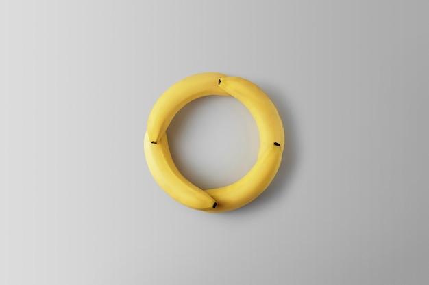 クリエイティブコンセプトゼロウェイスト。灰色の背景に丸い形のバナナ。