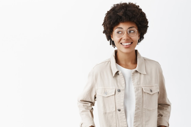 Creative confident and carefree dark-skinned female freelancer in beige shirt and glasses holding hands in pockets gazing left joyfully, spending great time over gray wall