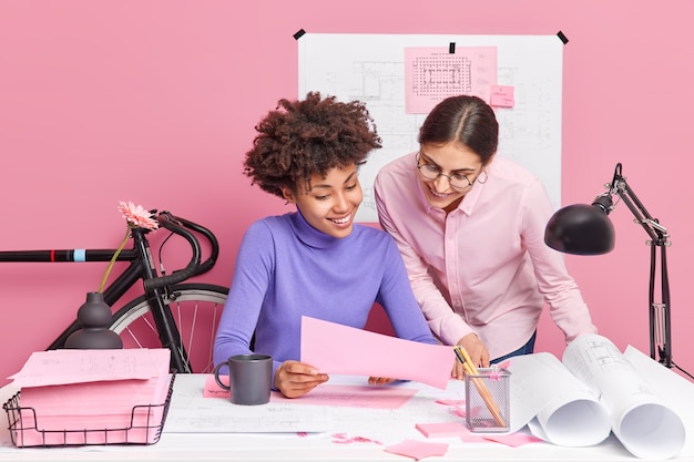 Creative cooperation and teamwork concept. two cheerful mixed race women collaborate together in coworking space discuss plan of working process prepare development project pose at cozy office