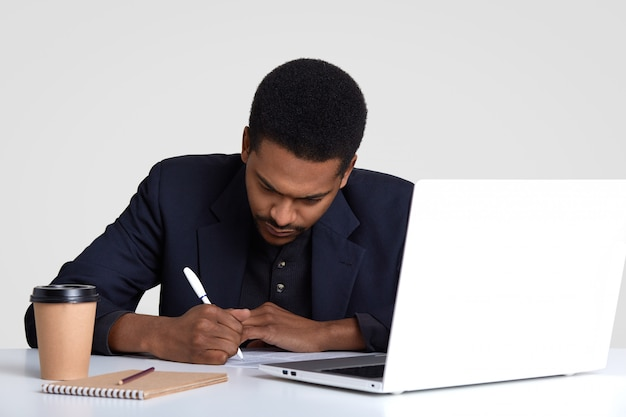 Creative copywriter writes down ideas, sits in front of opened laptop computer, surrounded with notepad, dispoasable cup of hot beverage, poses at work place, isolated on white.