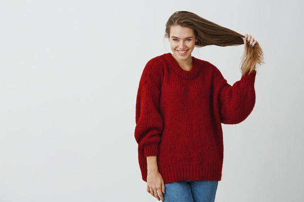 Creative coworker flirting with handsome guy during break. studio shot of good-looking feminine european woman in loose red sweater, pulling hair and smiling broadly, taking good care about health