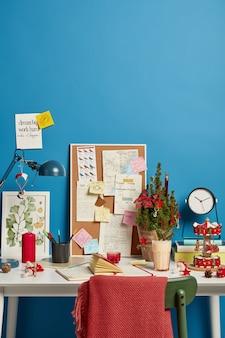 Luogo di lavoro decorato creativo di studente o scienziato, blocco note chiuso sul tavolo, scrivania con note scritte a mano incollate