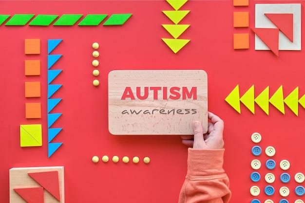 4 월 2 일 자폐증 세계의 날을위한 크리에이티브 디자인입니다. 텍스트 세계 자폐증의 날이있는 손 잡고 나무 보드