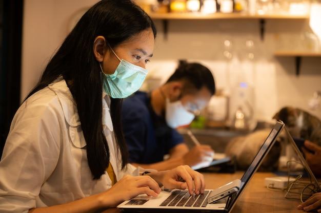 Креативный дизайнер бизнес-работника, работающий в разнесенном и носящем медицинскую маску для лица.