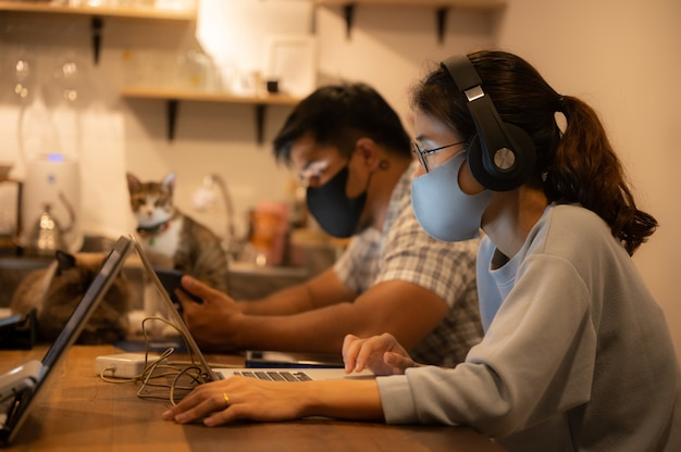 Creative designer business worker, working in spaced and wearing a medical face mask to prevent the spread of the coronavirus covid-2019, home office for  small people group to work from home