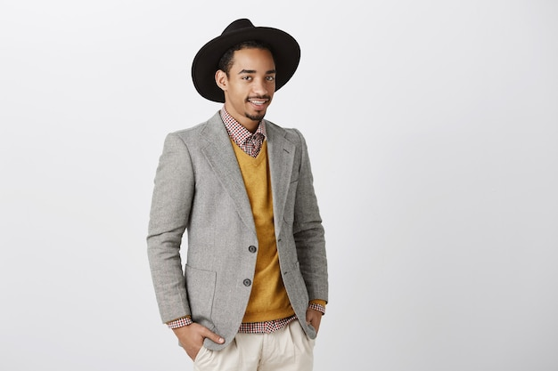 ファッションショーを議論する創造的なデザイナー。スタイリッシュなジャケットと帽子の見栄えの良いダークスキンの男性モデル。半回転して立って、灰色の壁越しに仕事やライフスタイルについて同僚とカジュアルに話します。