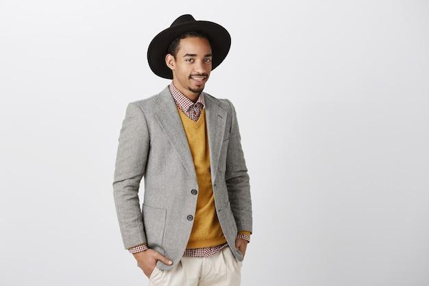 Designer creativo discutendo sfilata di moda. bello modello maschio dalla pelle scura in giacca e cappello alla moda, in piedi mezzo girato, parlando casualmente con i colleghi del lavoro e dello stile di vita oltre il muro grigio