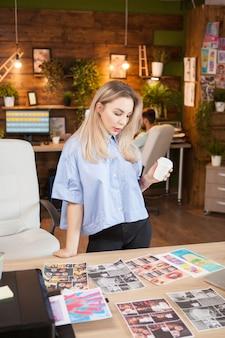 彼女の次のファッションコンセプトについて考えているコーヒーのカップを保持しているクリエイティブデザイナー。