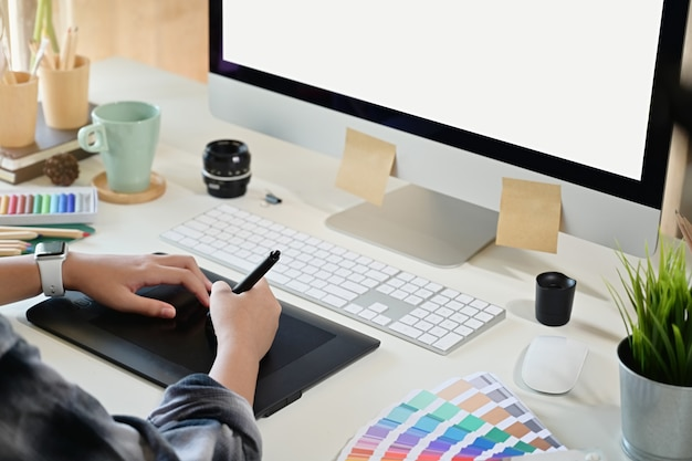 Creative designer using digital drawing tablet in studio workplace