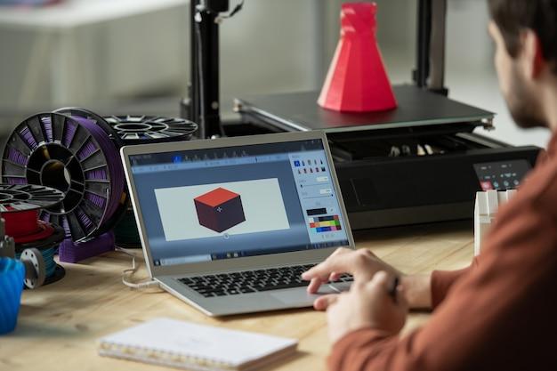 사무실의 특수 장비에 인쇄하기 전에 노트북 화면에서 새로운 3d 모델을 작업하는 크리에이티브 디자이너