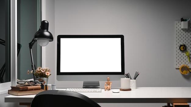 Креативное дизайнерское рабочее место с компьютером и оборудованием на белом столе