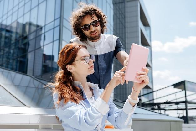 크리에이티브 디자이너. 남자 친구를 기다리는 동안 책을 읽고 안경을 쓰고 젊은 매력적인 여자
