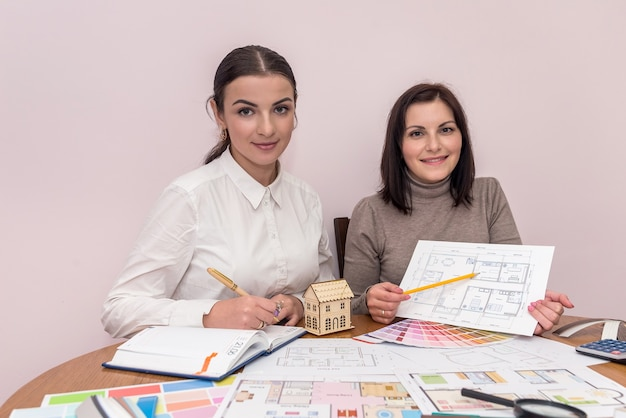 Creative designers showing house plan and posing