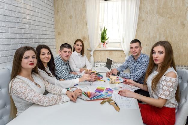 Команда креативных дизайнеров работает над проектом нового дома
