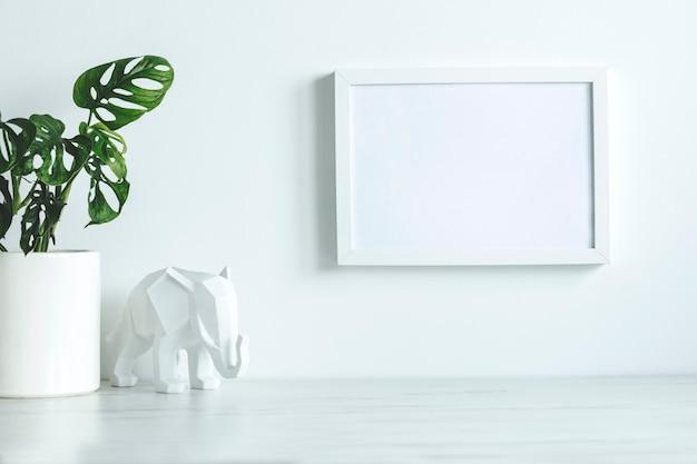 스칸디나비아 스타일의 창의적인 책상, 흰색 모의 포스터 프레임, 흰색 코끼리 그림, 클래식 냄비에 식물. 흰색 최소한의 개념입니다.