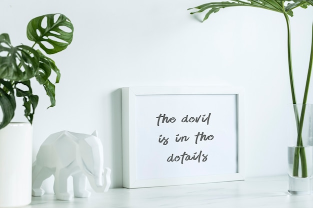 흰색 모의 포스터 프레임, 흰색 코끼리 그림, 고전적인 냄비에 심고 유리 꽃병에 잎을 넣은 스칸디나비아 스타일의 창의적인 책상. 흰색 최소한의 개념입니다.