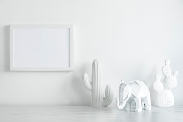 Creative desk in scandinavian style with white mock up frame and white figure of cacti and elephant