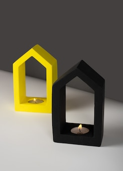 크리에이 티브 대각선 아이소메트릭 프로젝션 구성입니다. 정물. 회색 벽에 그림자입니다. 집 모양의 콘크리트 촛대 검은 색과 노란색 색으로 소이 왁스를 태우는 향초. 미니멀리즘