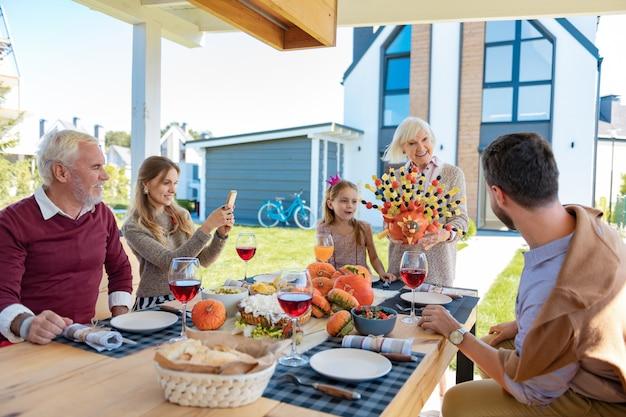 창작 요리. 축제 테이블에 앉아있는 동안 전화로 밝은 금발 소녀 복용 사진
