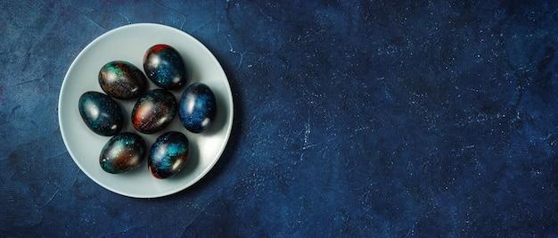 Креативные пасхальные яйца в тарелке на темно-синем фоне