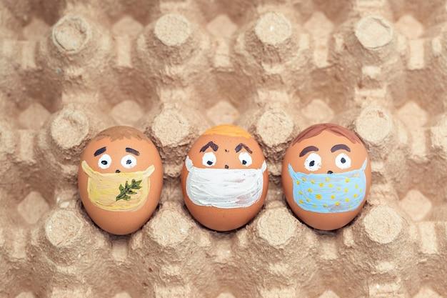 コロナウイルス(covid19)保護の概念を持つ創造的なイースターエッグ。医療用マスクを身に着けている落書きの顔を持つ多様な鶏の卵。