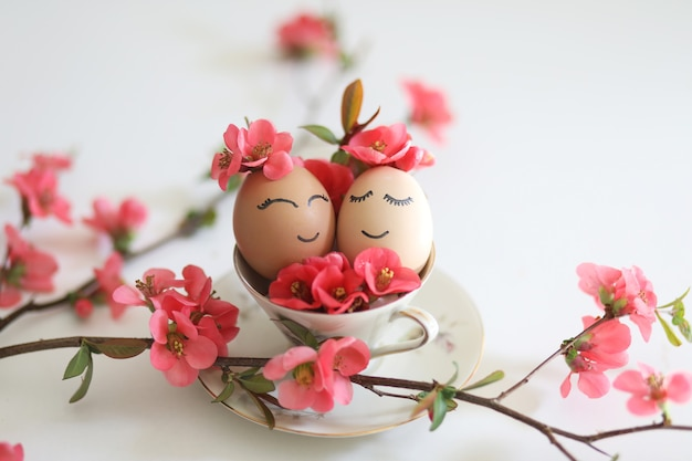 Creative easter eggs with cute face sleepy eyes and spring flowers in tea cup on white background