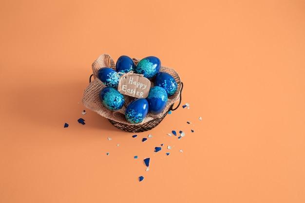 カラフルな卵と青の背景に花で作られた創造的なイースターレイアウト。サークルリースフラットレイアウトコンセプト。イースター休暇のコンセプトです。