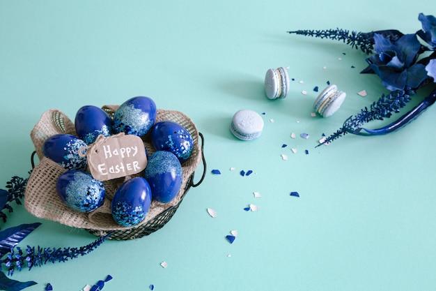 カラフルな卵と青の花で作られた創造的なイースターレイアウト。