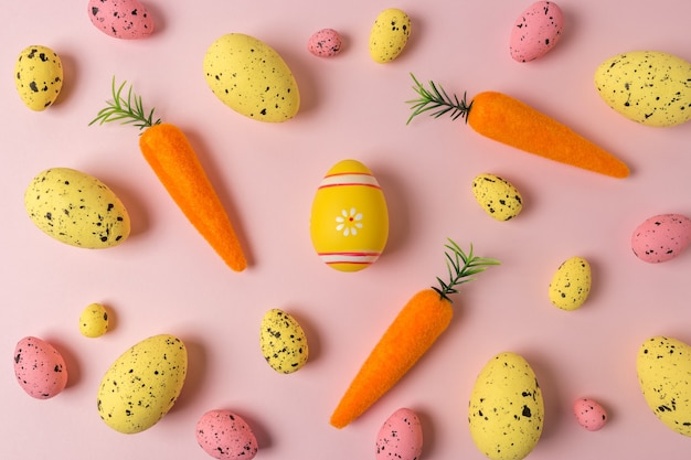 ピンクのニンジンとカラフルな卵の創造的なイースターパターン。