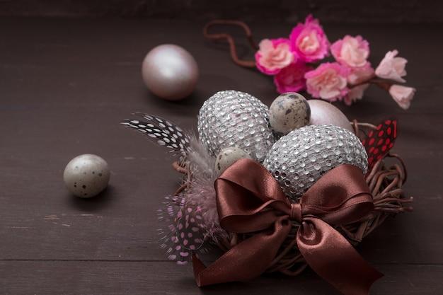 Креативный пасхальный натюрморт с гнездом с яйцами в стразах с бантом и цветущей веткой в неброском ключе