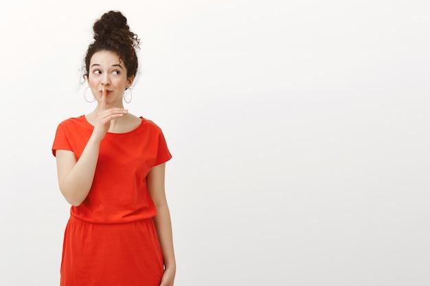 세련 된 빨간 드레스에 곱슬 머리를 가진 창조적 인 감정적 인 행복 한 여자, 오른쪽을보고 쉿 말하면서 광범위하게 웃고